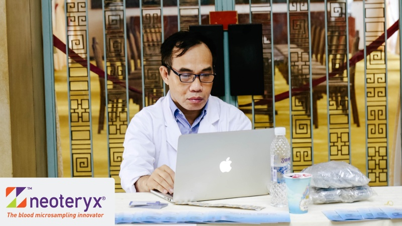 A doctor works on a laptop representative of being able to work with his patients remotely via the internet