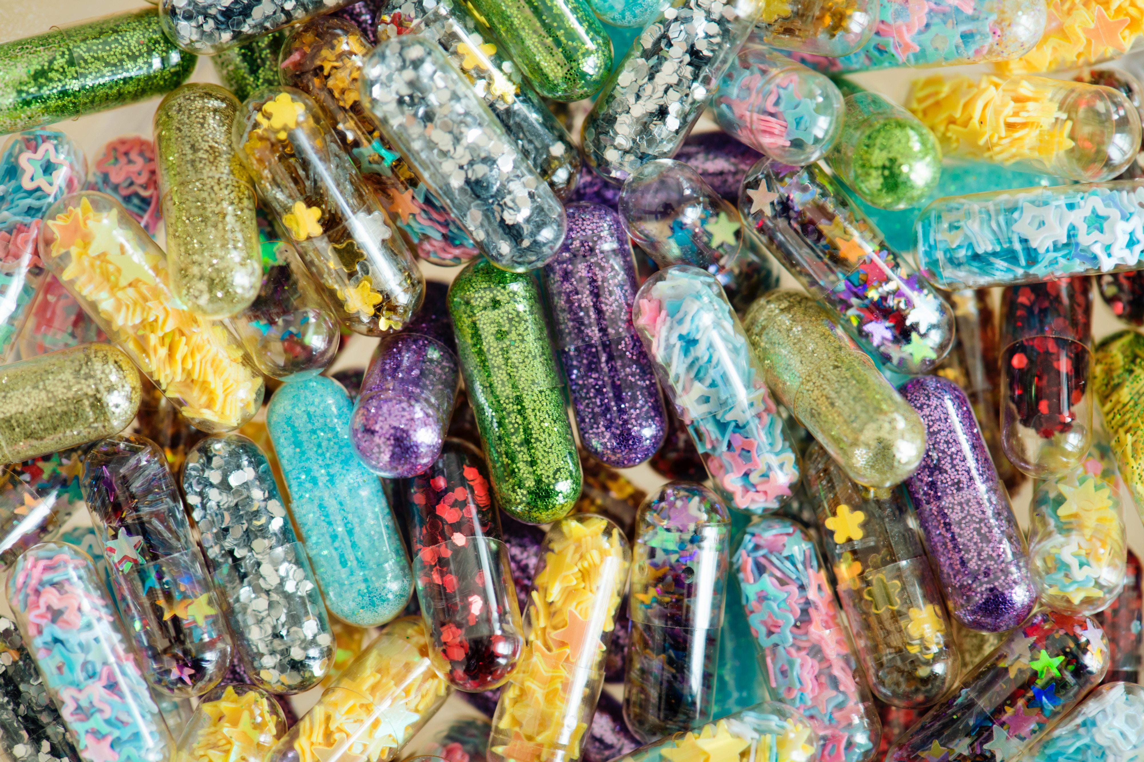 Ein Stapel durchsichtiger Tabletten, die mit Pailletten und Konfetti gefüllt sind